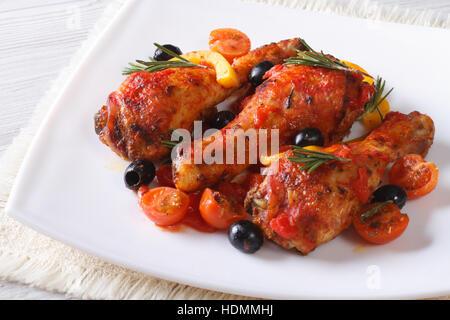 Geschmorte Hähnchenschenkel in Tomatensauce mit Paprika, Oliven und Rosmarin auf einem weißen Teller, horizontale - Stockfoto