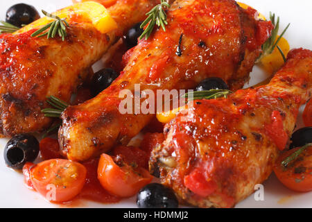 Leckere Hähnchenkeulen in Tomatensauce mit Paprika, Oliven und Rosmarin auf einem weißen Teller, Makro horizontale - Stockfoto