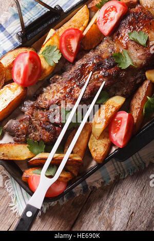 Schweinefleisch, Kartoffeln und Tomaten Nahaufnahme auf einer Grillpfanne. vertikale Ansicht von oben - Stockfoto