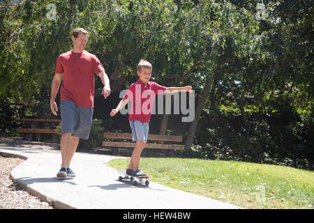 Junge mit Vater üben auf Skateboard im park - Stockfoto