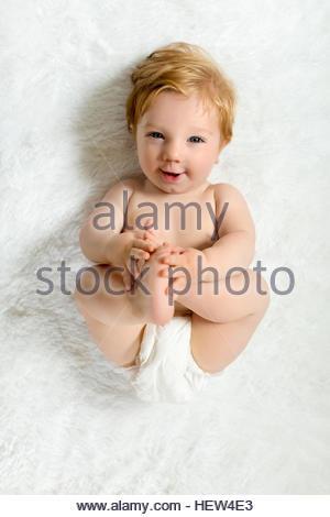 Kleinkind auf Decke liegend, Füße, hält lächelnd - Stockfoto