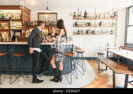 Kellnerin serviert junges Paar in cocktail-bar - Stockfoto