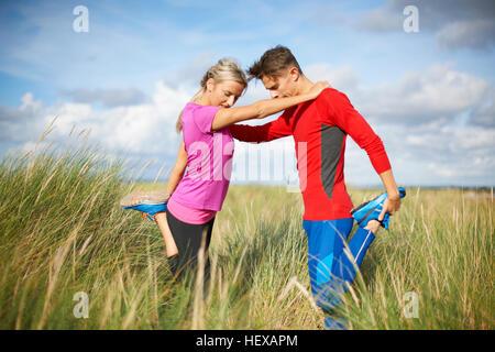 Paar in hohe Gräser auf einem Bein tun stretching-Übungen - Stockfoto