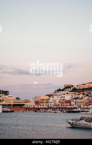 Der Mond aufgeht über den Hafen der Insel Ponza, Italien, in der Dämmerung kurz nach dem Sonnenuntergang. - Stockfoto