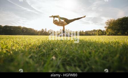 Mann und Frau paar Yoga im Freien auf dem Rasen zu tun. Passen Sie junges Paar üben Acroyoga. Mann heben und balancing - Stockfoto