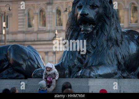 Ein junges Mädchen sitzt unter einer der vier riesigen Löwen-Statuen an der Basis der Nelsonsäule, am 17. Januar - Stockfoto