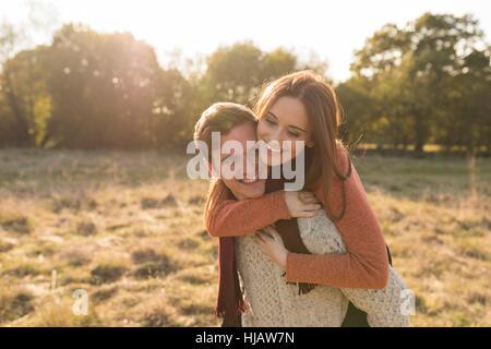 Junges Paar in ländlicher Umgebung, junge Mann geben junge Frau Huckepack - Stockfoto