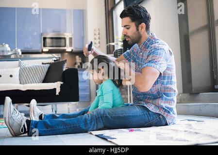 Vater sitzt am Boden Tochter Haare tun - Stockfoto