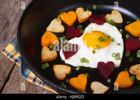 Romantisches Frühstück mit Spiegeleiern und Gemüse in der Form von Herzen hautnah in einer Pfanne - Stockfoto