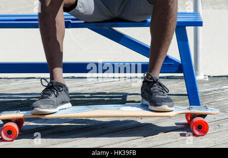 Männliche Füße auf Skateboard sitzend auf einer Bank - Stockfoto
