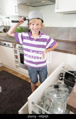 Fröhlicher Junge mit Pan am Kopf in Küche, Bayern, Deutschland - Stockfoto