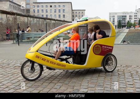 BERLIN, Deutschland - 23 Mai: Ein Taxi Bike zeigt Touristen ein Überbleibsel der Berliner Mauer am 23. Mai 2014 - Stockfoto