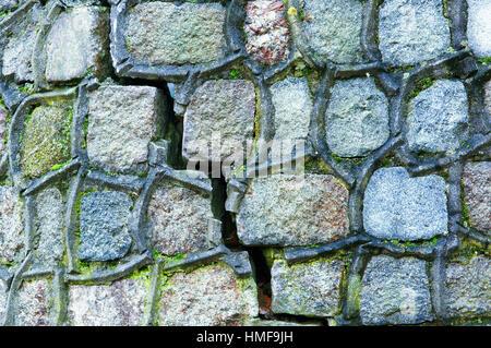 ein Riss in der Wand, grünes Moos bedeckt die alte Steinmauer - Stockfoto