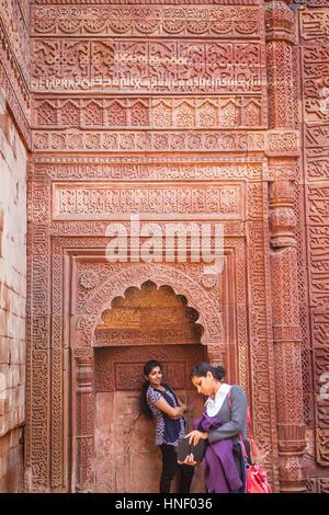 Geschnitzte Wand und Besuchern in Qutub Minar Komplex, Delhi, Indien - Stockfoto