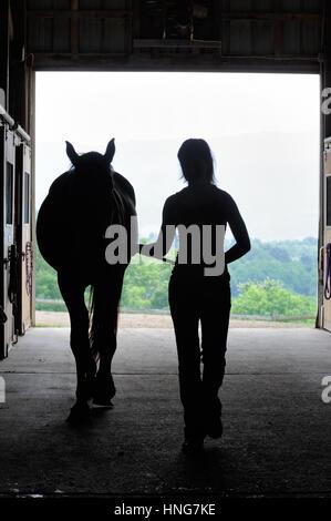 Junge Frau mit Pferd in offenen Scheunentor Silhouette zu Fuß von der Öffnung. - Stockfoto