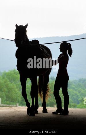 Junge Frau mit Pferd in offenen Scheunentor Silhouette Verschärfung ihrer Sattelgurt gehen reiten. - Stockfoto