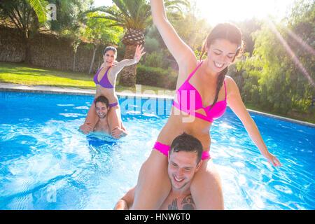 Freunde im Schwimmbad herumalbern - Stockfoto