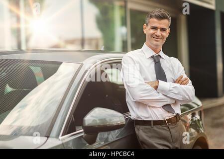 Geschäftsmann lächelnd in die Kamera und lehnte sich gegen seinen teuren Neuwagen, Autohaus und Business-Konzept - Stockfoto