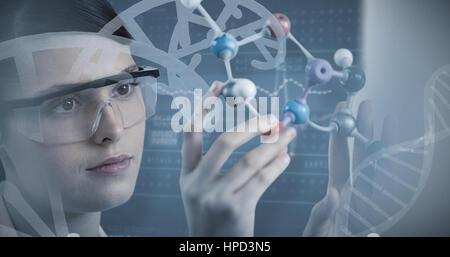 Nahaufnahme der Wissenschaftler hält Molekülmodell gegen Panoramablick auf Daten auf Bildschirm des Geräts - Stockfoto