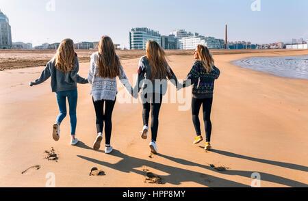 Spanien, Gijon, Rückansicht der vier Freunde laufen Hand in Hand am Strand - Stockfoto