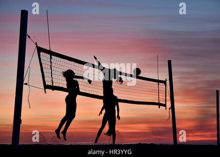 Silhouetten von weiblichen Volleyballspieler üben Volleyball am Strand bei Sonnenuntergang in Mission Beach, San - Stockfoto