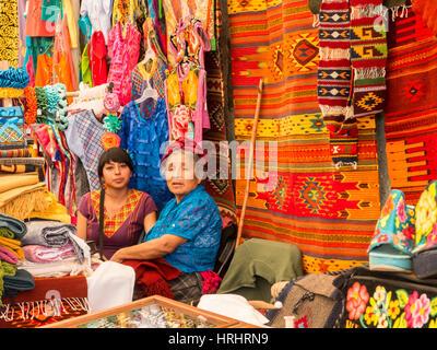 Frauen reden im Markt mit Hintergrund handgeknüpfte Teppiche und Kleidung, Oaxaca, Mexiko, Nordamerika - Stockfoto
