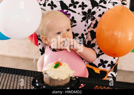 Babymädchen sitzen im Hochstuhl, Geburtstagskuchen Essen - Stockfoto