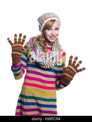 Süße fröhliche Teenager-Mädchen tragen bunt gestreiften Pullover, Schal, Handschuhe und Mütze isoliert auf weißem - Stockfoto