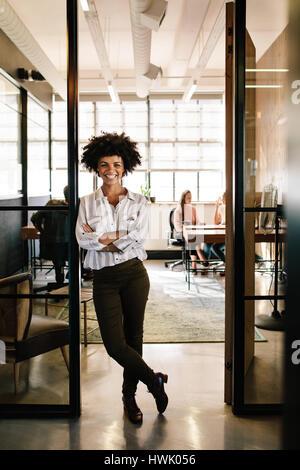 In voller Länge Portrait von erfolgreichen jungen Frau gelehnt zu Büro Tür Arme gekreuzt. Weibliche Führungskraft - Stockfoto