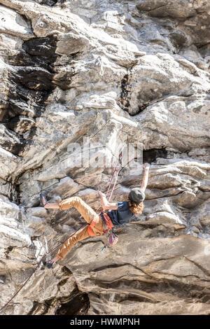 Ein unbekannter junger Mann klettert eine sehr schwierige Route entlang der Q'emilin Wanderwege in Post Falls, Idaho. - Stockfoto