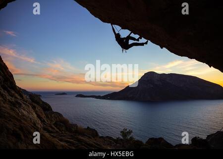 Junger Mann Klettern entlang der Decke der Höhle bei Sonnenuntergang, Kalymnos Insel, Griechenland. Schönen Abend - Stockfoto