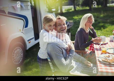 Glücklich, liebevoller Vater und Tochter umarmt außerhalb sonnige Wohnmobil - Stockfoto