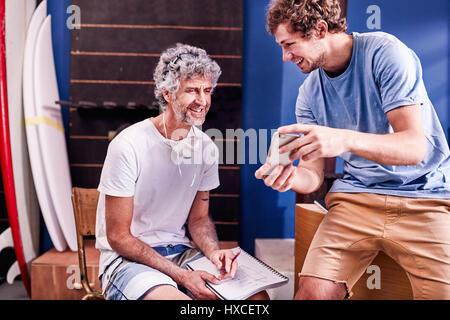 Männliche Surfbrett Designer mit Handy Brainstorming in der Werkstatt - Stockfoto