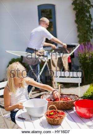 Dänemark, Mon, Mädchen (12-13) sortieren Obst am Tisch, Mann im Hintergrund hängenden Kleidungsstücken - Stockfoto