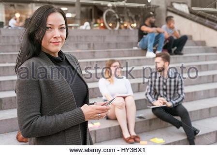 Schweden, Skåne, Malmö, reife Frau mit Smart Phone und junge Leute sitzen auf Schritte im Hintergrund - Stockfoto