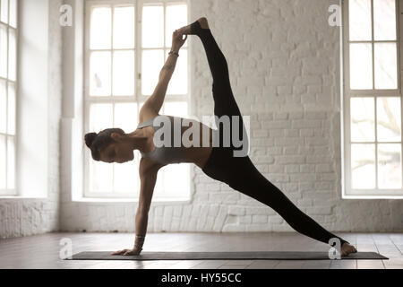Junge Frau in Full Version Vasisthasana Pose, weiße loft - Stockfoto