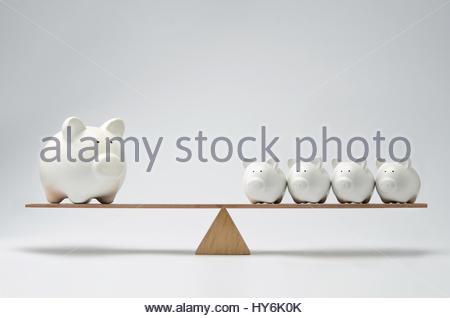 Kleinen Sparschweine und große Sparschwein balancieren auf einer Wippe - Stockfoto