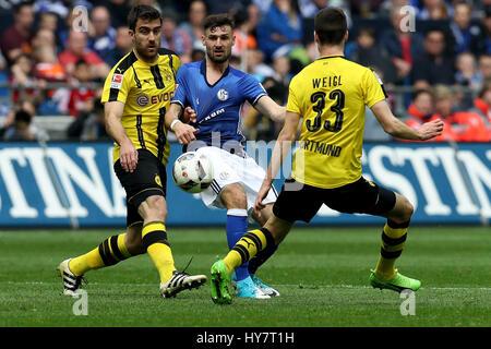 Gelsenkirchen. 1. April 2017. Daniel Caligiuri (C) des FC Schalke 04 wetteifert mit Sokratis Papastathopoulos (L) - Stockfoto