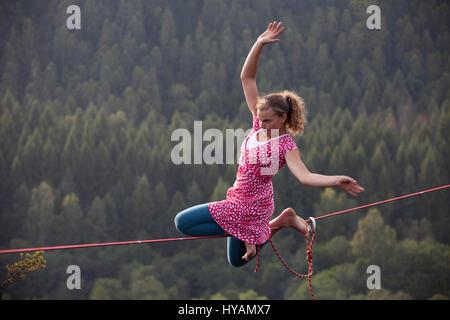 OSTROV, Tschechien: ein weiblicher Slackliner zeigt auf dem Hochseil. VON Verkleidung Kostüm Verleih-Draht Yoga - Stockfoto