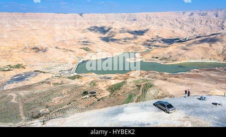 DHIBAN, Jordanien - 20. Februar 2012: Menschen am Aussichtspunkt über Al Mujib Staudamm am Fluss Wadi Mujib auf - Stockfoto
