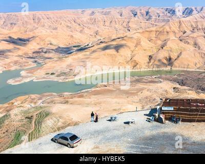 DHIBAN, Jordanien - 20. Februar 2012: Touristen am Aussichtspunkt über Al Mujib Staudamm am Fluss Wadi Mujib auf - Stockfoto