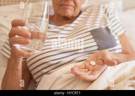 Ältere Frau im Bett Einnahme am Morgen - Stockfoto