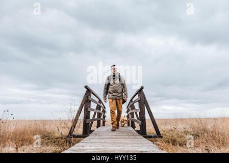 Wanderer und Hund überqueren Holzbrücke am bewölkten Tag - Stockfoto