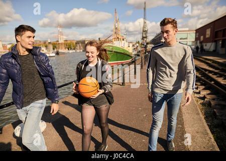 Drei Freunde, die zu Fuß neben Fluss, junge Frau, die Basketball, Bristol, UK - Stockfoto