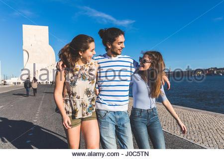 Drei Freunde, zu Fuß auf dem Seeweg, Denkmal der Entdeckungen im Hintergrund, Lissabon, Portugal - Stockfoto