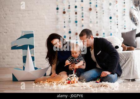 Junge Eltern sitzen auf Teppich und spielt mit ihrem Baby. Sie Lächeln und sehr leidenschaftlich sind. - Stockfoto