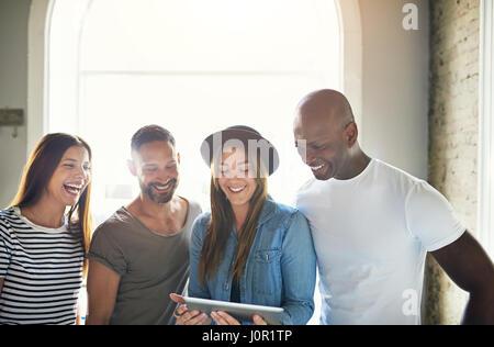 Junge stilvolle Gruppe von vier Freunden halten touch-Pad und breit lächelnd auf Hintergrund des Fensters. - Stockfoto