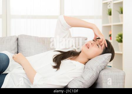 Junge Frau mit Kopfschmerzen auf Couch zu Hause. Casual-Style indoor Shooting. Lebensstil und Gesundheit Konzept - Stockfoto