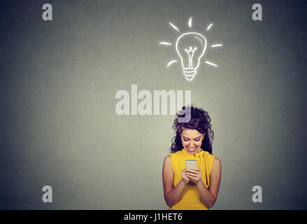 Ziemlich zufrieden, junge Frau hält mit Smartphone überragt grauer Hintergrund Tafel mit Glühbirne über Kopf und - Stockfoto