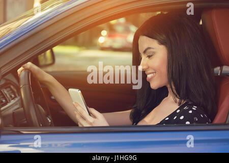 Lächelnde Frau SMS während der Fahrt zur Arbeit - Stockfoto